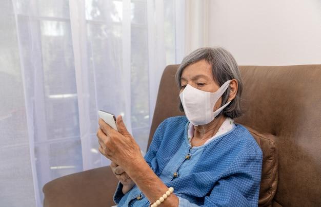 Covid19-pandemie ältere frau entspannt sich im wohnzimmer beim surfen im drahtlosen internet auf dem handy