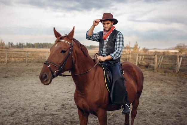 Cowboy, der ein pferd auf einer ranch reitet, westlich
