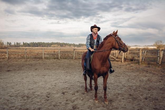 Cowboy, der ein pferd auf einer ranch reitet