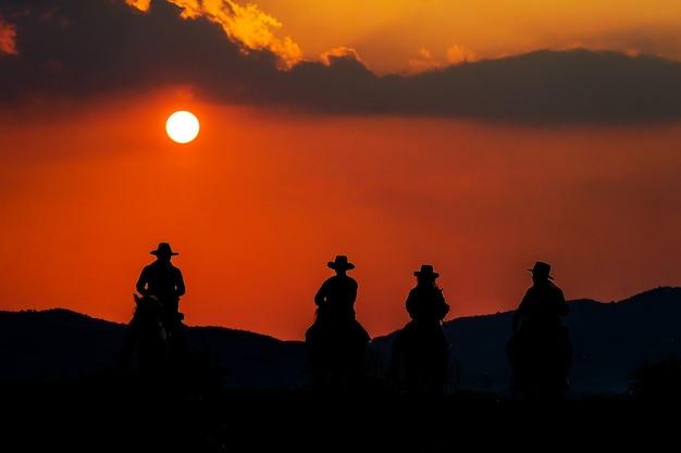 Cowboy, der ein pferd nahe der sonne reitet
