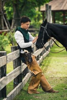 Cowboy, der sein pferd auf dem gebiet nahe zaun bearbeitet