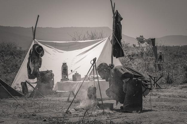 Cowboys setzen feuer, um wasser in ländlichen gebieten mit bergen zu kochen.
