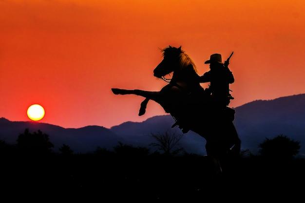 Cowboyschattenbild auf einem pferd während des netten sonnenuntergangs