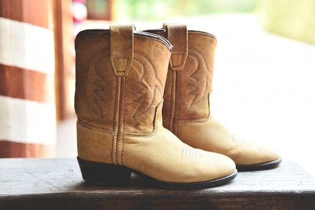 Cowboystiefel american wild west retro-cowboyrodeo-paare der traditionellen ledernen roper-art western auf hölzerner weinleseart in der landschaft