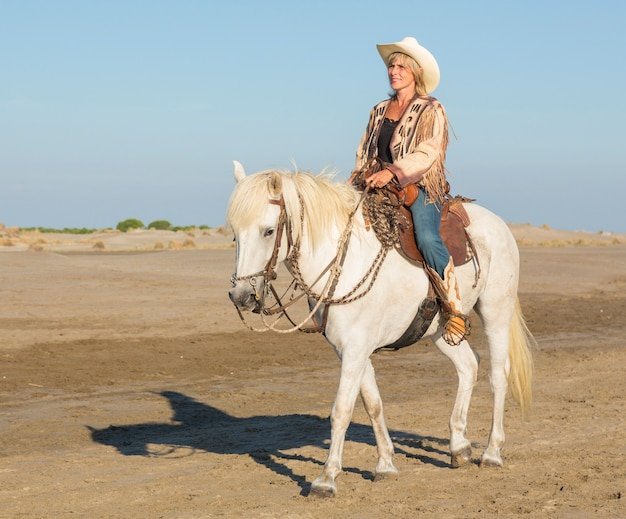 Cowgirl auf camargue-pferd