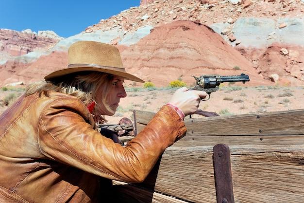 Cowgirl mit einer waffe in der hand, bereit zu schießen