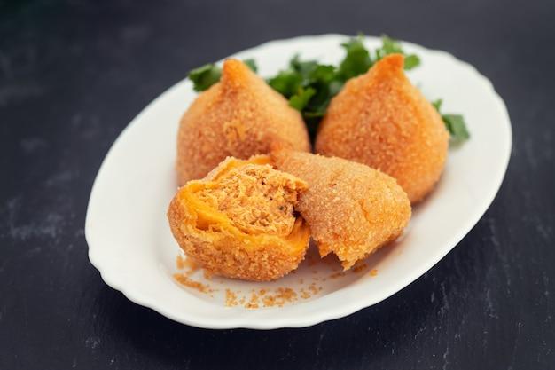 Coxinha de frango, typisch brasilianische hühnerkrokette auf weißem teller