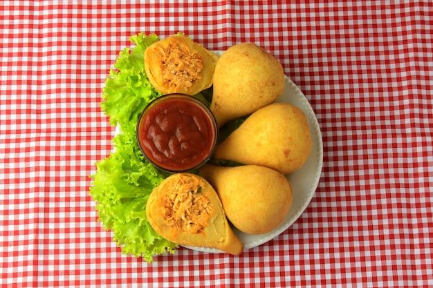 Coxinha im teller, traditionelle brasilianische küchensnacks gefüllt mit huhn