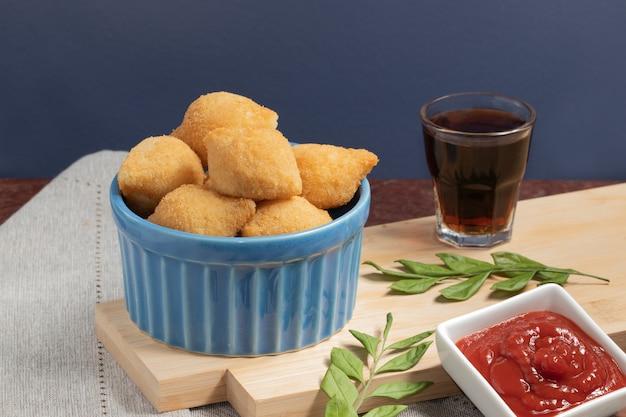 Coxinha vom hühnchen serviert mit soda und ketchup.