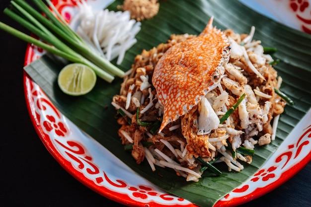 Crab pad thai serviert mit limetten, schalotten, sojasprossen. zerkleinertes erdnuss- und chilipulver.