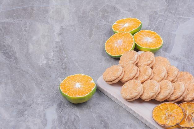 Cracker auf einer holzplatte mit orangenscheiben herum