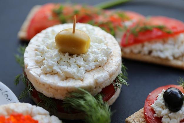 Cracker burger mit ricotta, dill, tomate und oliven.
