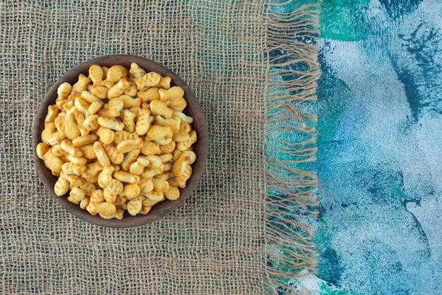 Cracker fisch in schüssel auf einer textur, auf dem marmortisch.