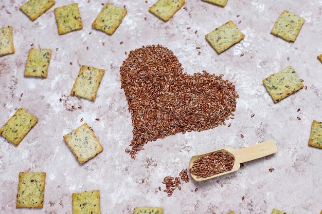 Cracker in form des herzens von den leinensamen mit olivenöl, leinensamen und grüns, draufsicht