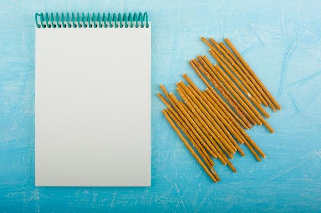 Cracker klebt mit einem leeren quittungsbuch auf dem blauen tisch