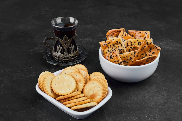 Cracker mit einem glas tee auf schwarz