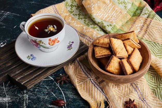 Cracker mit einer tasse kräutertee.