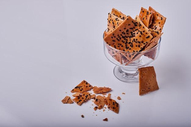 Cracker mit kreuzkümmel in einer glasschale.