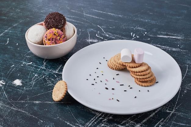 Cracker mit marshmallow-keksen in weißen schalen, draufsicht.