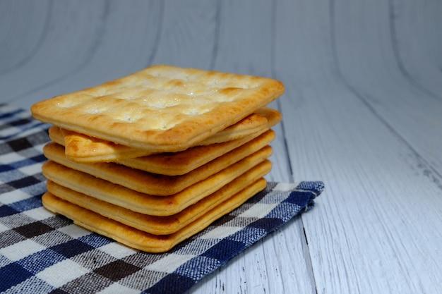 Cracker-quadrate gestapelt, cracker-quadrate gestapelt auf kariertem stoff, cracker-quadrate gestapelt