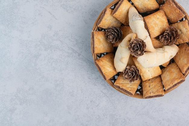 Cracker und kekse in schüssel mit tannenzapfen. foto in hoher qualität