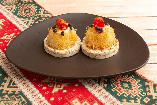 Cracker und kuchen in brauner platte auf creme rustikal