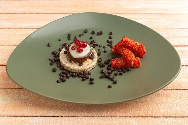 Cracker und kuchen in grüner platte mit nougat-kaffeesamen und cranberries-kuchen auf sahne