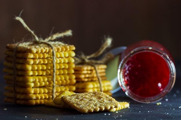 Cracker werden mit hanfseil und erdbeermarmeladenflasche auf tabelle in der dunkelheit gebunden