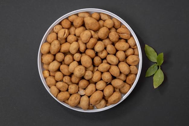 Crackernüsse, japanische erdnüsse oder erdnüsse nach japanischer art, ein snack aus erdnüssen, die mit einem weizenmehlteig überzogen und dann gebraten werden