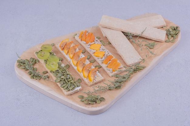 Crackersandwiches mit kräutern und früchten auf einem holzbrett