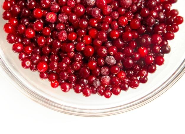 Cranberries in einer glasschüssel auf einer weißen oberfläche