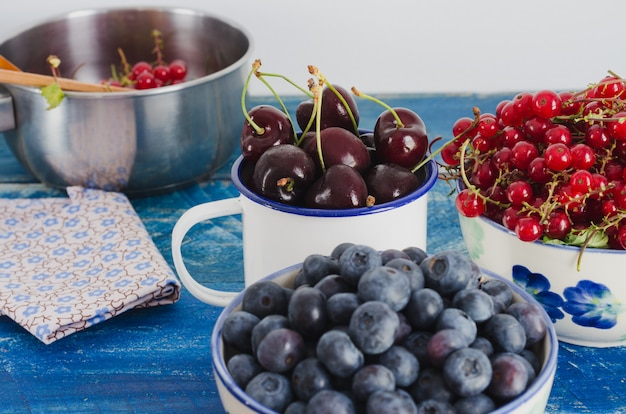 Cranberries kirschen und johannisbeeren in der weißen schüssel auf gealtertem hölzernem hintergrund der blauen farbe.