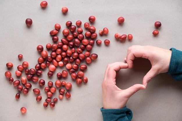 Cranberries verstreut auf recyceltem braunem papier, weibliche hände, die herzzeichen zeigen. rohe frische cranberry-beere, ansicht von oben. cranberry hintergrund, draufsicht, flach lag auf bastelpapier