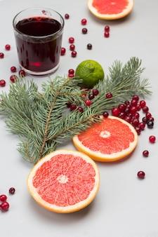 Cranberry-getränk im glas. grapefruit- und preiselbeerscheiben, tannenzweige auf dem tisch.