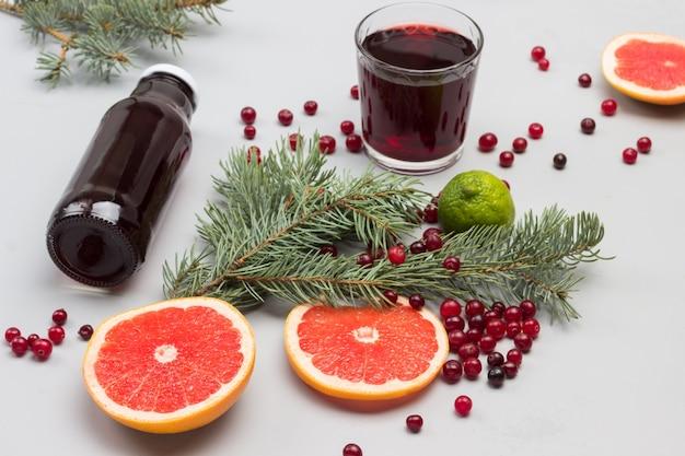 Cranberry-getränk im glas und in der flasche. grapefruit- und preiselbeerscheiben, tannenzweige auf dem tisch