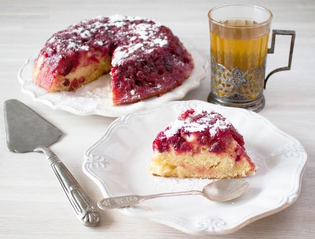 Cranberry tart pie cake, weiße keramikplatte, teelöffel, teeglas, getränkehalter, kochspatel