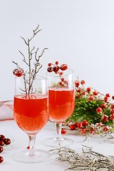 Cranberrysaft mit weihnachtsverzierung auf weißer oberfläche.