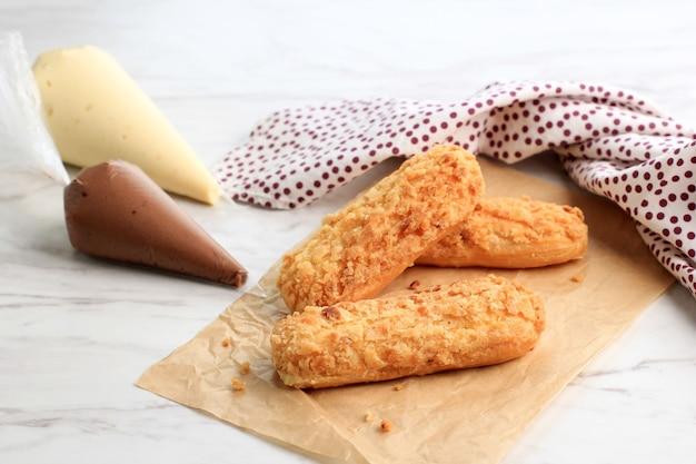 Craquelin choux/eclair kekse mit köstlicher sahnefüllung auf marmorhintergrund. fertig zum befüllen mit sahne
