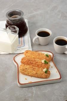 Craquelin eclair, köstliches französisches brandteiggebäck-dessert mit tigermotiven oben (craquelin), garniert mit minzblatt und sahne. serviert mit kaffee