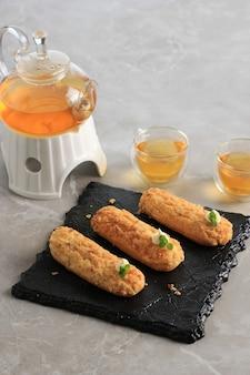 Craquelin eclair, köstliches französisches brandteiggebäck-dessert mit tigermotiven oben (craquelin), garniert mit minzblatt und sahne. serviert mit tee