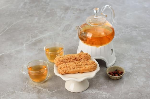 Craquelin eclair, köstliches französisches choux-gebäck-dessert mit tigermotiven an der spitze (craquelin), serviert mit kaffee. bäckerei-tea-time-konzept auf grauem marmor