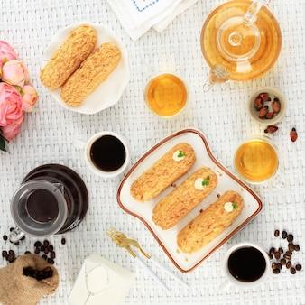 Craquelin eclair, köstliches französisches choux-gebäck-dessert mit tigermotiven an der spitze (craquelin), serviert mit kaffee. bäckerei-tea-time-konzept