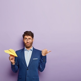 Creative director hält papier aus gelbem flugzeug, hat verwirrten blick