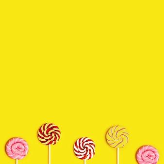 Creative flat lag mit süßen runden bonbon-lollypops mit streifen auf stick auf gelb