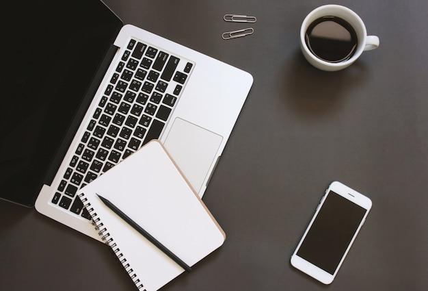 Creative flat lay design von arbeitsbereich schreibtisch mit laptop, notebook, smartphone und kaffee mit kopie raum hintergrund