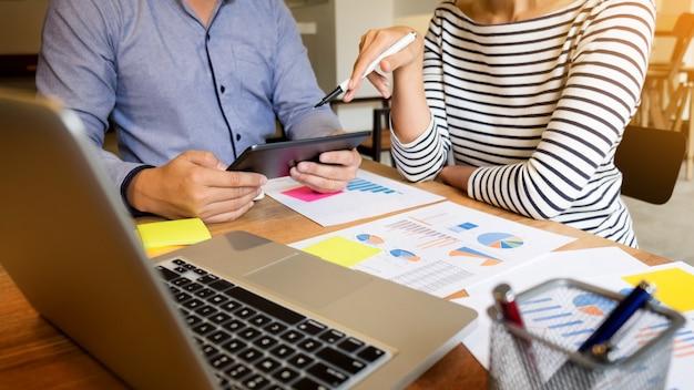 Creative team job junge geschäftsmann arbeitet mit startup-projekt analysieren grafik-pläne und diskutieren auf arbeitsbereich büro, brainstorm sitzung konzept.