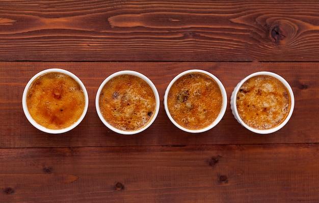 Crème brlée in einer weißen schüssel mit zuckerkruste. studiofotografie. landhausstil.