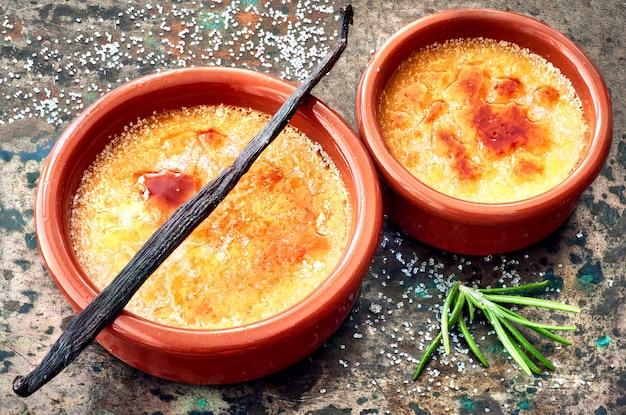 Creme brulee (creme brulee, gebrannte sahne) mit vanillestift in terracota-auflaufformen