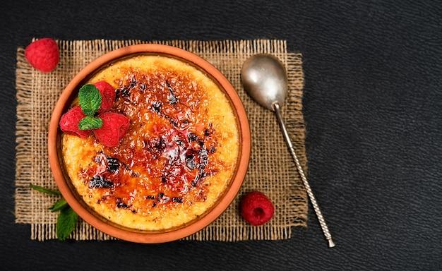 Creme brulee dessert aus sahne und rohrzucker mit frischen himbeeren und minzblättern auf einem dunklen tisch, layout mit kopierraum. leckere desserts in einem café oder restaurant