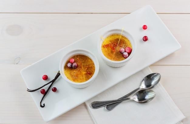 Creme brulee dessert mit preiselbeeren in einer weißen schüssel